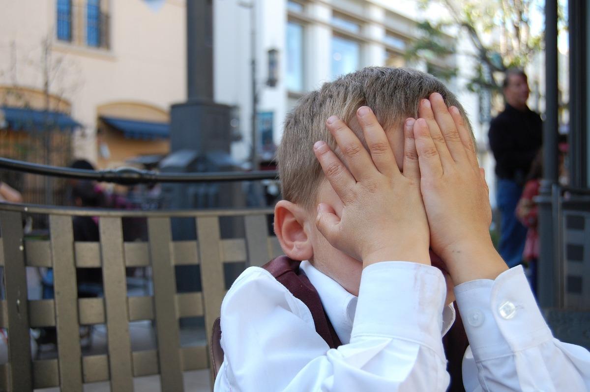 Boy child shy ashamed hands covering face