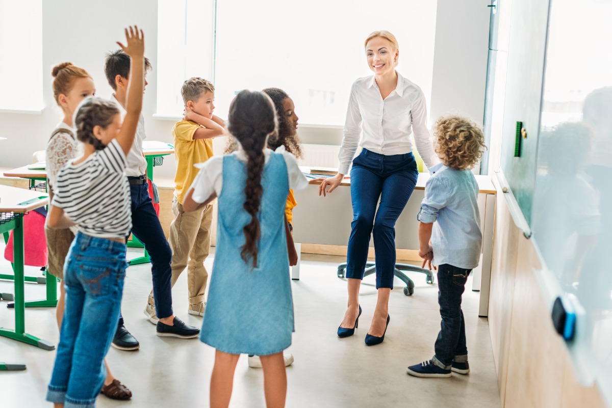 children teacher standing in classroom hand raised