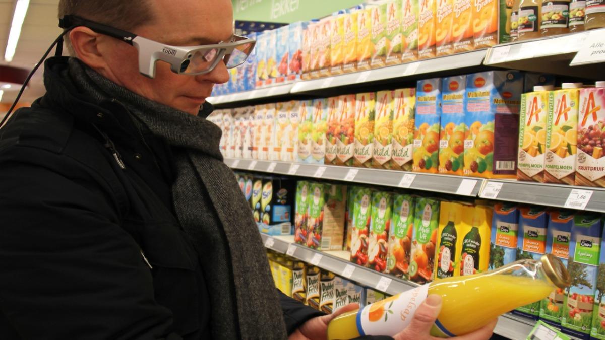 man supermarket holding juice with eyetracking glasses