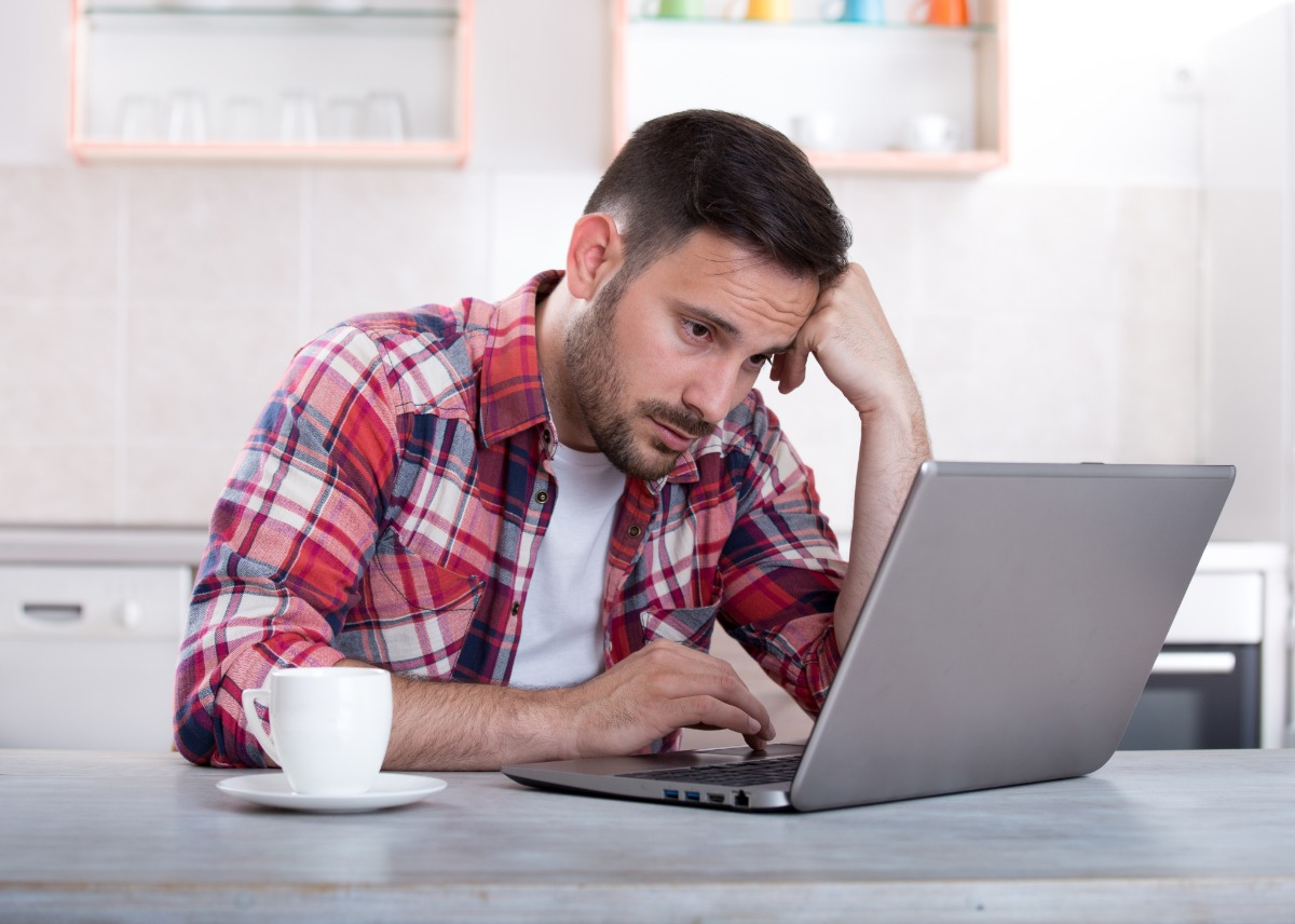 Man with laptop looking frustrated