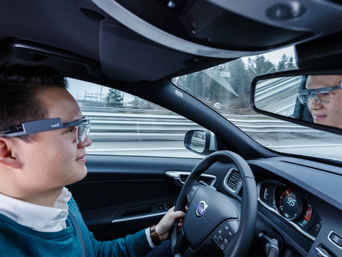 man with tobii eye tracking glasses driving in a car
