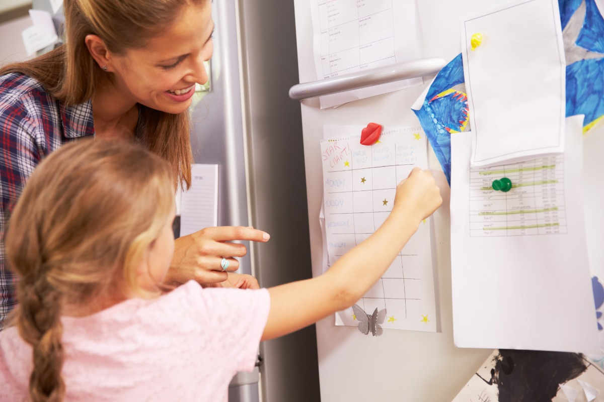 Mother child drawing on refrigerator