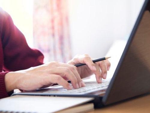 news flash grant assistance program hands typing laptop reversed