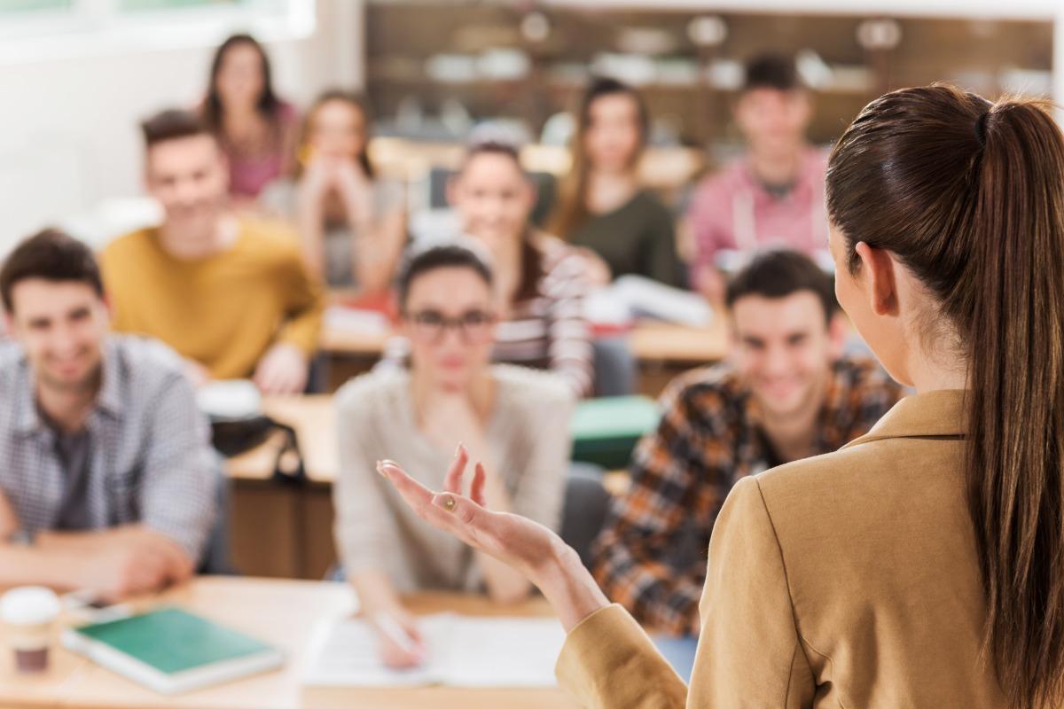 Female teacher classroom students debriefing